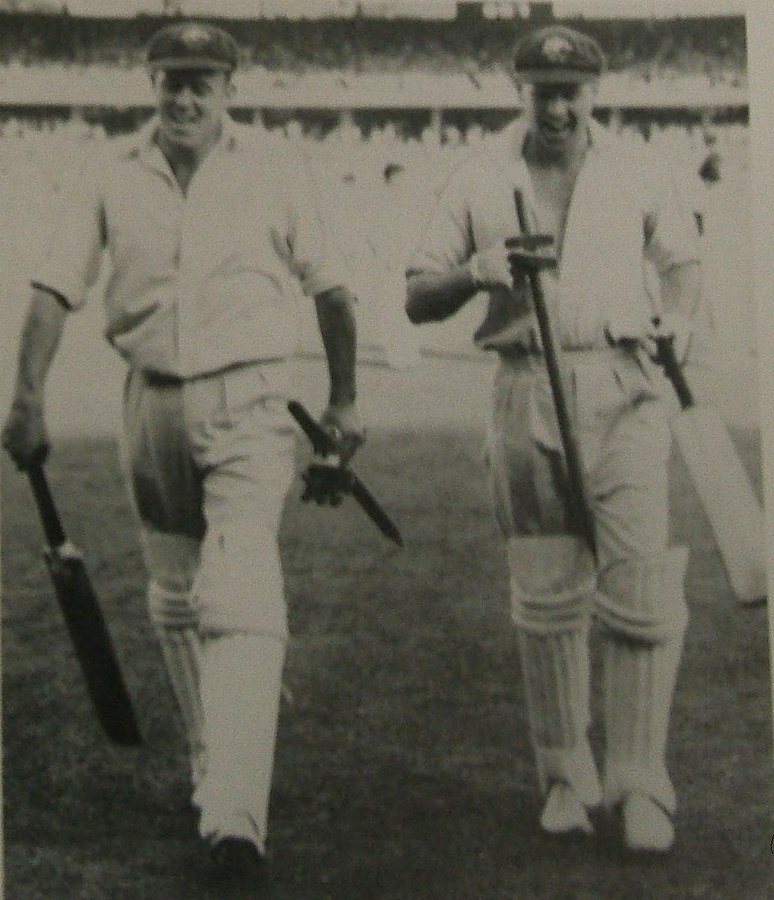 Ring (right) and Bill Johnston (left) leave the field after their unbroken last wicket stand guided Australia to victory over the West Indies in the Fourth Test at the MCG in 1951–52.