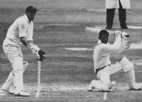 The defiant Kunderan goes down on one knee to drive Hobbs. Murray who equalled a world wicket keeping record is poised over the stumps.